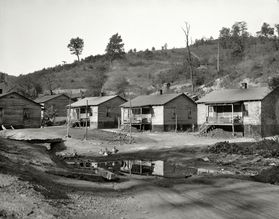 black and white photo of a row of small houses with a nearly-bare hillside in the background
